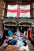 Huge Union Jack Flag outside the Blind Beggar pub in London's East End at Whitechapel Market. The Muslim population in this area is by a huge amount the most predominant, with Bangladeshi's making up some 55% of the local people.