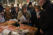 A fishmonger serves a woman customerat his stall in the Athens Central Market on Athinas Street. Athens, Greece