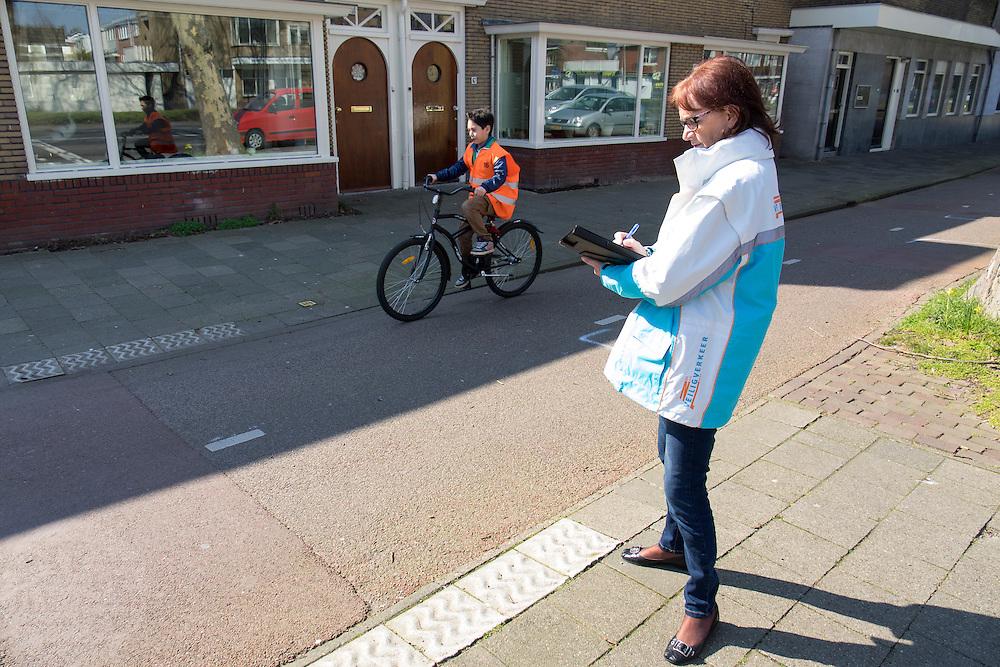 Een vrijwilliger van Veilig Verkeer Nederland kijkt of een deelnemer van het verkeersexamen zich goed gedraagr in het verkeer. In Utrecht zijn leerlingen van een basisschool bezig met de praktijk van het verkeersexamen. Het examen is onderdeel van de verkeerseducatie voor basisschoolleerlingen. Tijdens de verkeerslessen worden de jongeren de regels van het verkeer bijgebracht en getoetst. Daardoor zijn de kinderen beter voorbereid op verkeersdeelname, met name met de fiets.<br /> <br /> In Utrecht pupils of an elementary school engaged in the practice of traffic exam. The exam is part of the road safety education for elementary school students. During the traffic classes, pupils are taught the rules of traffic and tested. As a result, the children are better prepared for driving in traffic, especially with the bicycle.