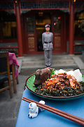 A plate of spicy chicken is arranged for a photograph at the Red Capital restaurant in Beijing, China, on Friday, April 11, 2008. Red Capital is an exercise in communist nostalgia, where the dishes have names like Socialist Economic Model and the pictures are of the late Chairman Mao Zedong and his cohorts.