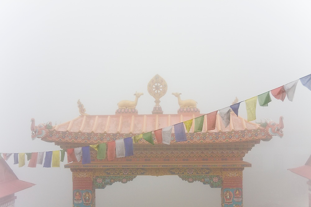 Tengboche Monastery gate and prayer flags in heavy mist, Khumbu (Everest) region, Sagarmatha National Park, Himalaya Mountains, Nepal.