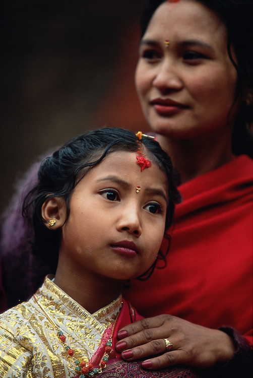 Newar woman with her daughter at the daughter's Ihi ceremony, a mock marriage to the Hindu god Vishnu, Patan, the Kathmandu Valley, Nepal. Among the Newars, who are the original inhabitants of the Kathmandu Valley, every girl goes through this ceremony sometime between the age of five and ten. The Ihi makes the girl a full member of her father's family and caste and is also said to make sure that she will never become a widow, even if later on her future human husband would die, since she will forever be married to the god Vishnu. The Ihi is therefore for the Newar women a protection against the stigmatization of widows otherwise common in Hindu culture.