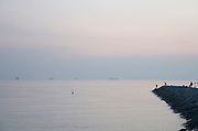 sunset with open sea and large ships at the horizon