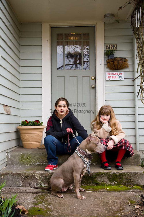 Margaret B. Jones and her daughter, Rya Hickey on the front porch of their home in Eugene, Oregon.  They are with their pit bull, Flue.