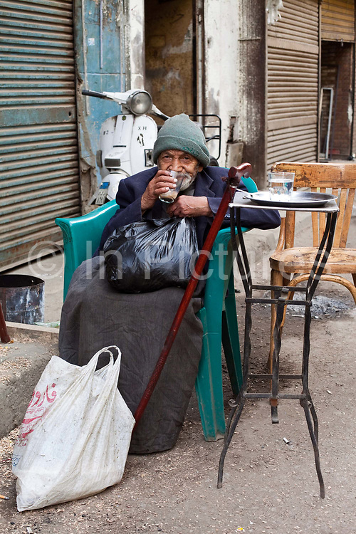 An old man drinks a cup of tea outside a coffee-house in the Bein al-Qasreen area, Islamic Cairo, Cairo, Egypt