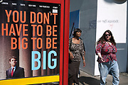 Women walk past a sign which reads You don't have to be big. London.