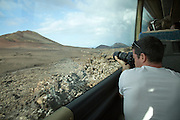 Tourists on tour bus on Ruta de Los Volcanes, Parque Nacional de Timanfaya, national park, Lanzarote, Canary Islands, Spain