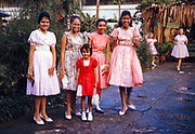 Sixth form girls, and a younger girl, dressed in pretty dresses for Bazaar Day, Bishop Anstey high school for girls, Port of Spain, Trinidad 1962