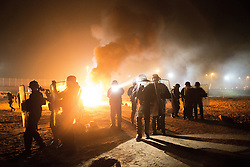 "© Licensed to London News Pictures . 23/10/2016 . Calais , France . Riot police in front of a fire set by residents , at the Calais migrant camp known as "" The Jungle "" , in Northern France , on the evening before the start of the eviction and destruction of the camp . Photo credit: Joel Goodman/LNP"