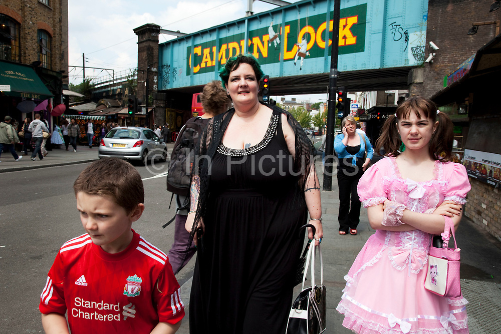 LONDON, ENGLAND, UK, JUNE 11TH 2011. Mother Louise Irwin-Ryan with her daughter Georgia (11, wearing a pink Lolita dress) and son Kiefer (8, wearing a red Liverpool Football Club kit) spending a day out together in Camden Town, North London. Here they are walking near to the famous sign for Camden Lock on the railway bridge. Louise is on various benefits to help support her family income, and housing, although recent government changed to benefits may affect her family drastically, possibly meaning they may have to move out of London. Louise Ryan was born on the Wirral peninsula in 1970.  She moved to London with her family in 1980.  Having lived in both Manchester and Ireland, she now lives permanently in North London with her husband and two children. Through the years Louise has battled to recover from a serious motorcycle accident in 1992 and has recently been diagnosed with Bipolar Affective Disorder. (Photo by Mike Kemp/For The Washington Post)