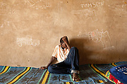 A former child soldier sits against a wall covered in drawings of firearms and military vehicles in a transit and orientation center for child soldiers in N'Djamena, Chad on Thursday June 10, 2010. Center workers ask children to draw anything they like as a way to understand how they feel and get a sense of what's on their minds.