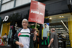 A pro-Palestinian activist canvasses support from the public outside a branch of JD Sports during a Boycott Puma day of action on 10th July 2021 in Slough, United Kingdom. The nationwide day of action was organised by Palestine Solidarity Campaign in protest against Puma's sponsorship of the Israeli Football Association, which includes clubs playing in Israeli settlements in the occupied West Bank, and in response to a call from Palestinians to mark the 16th birthday this week of the Boycott, Divestment and Sanctions (BDS) movement.