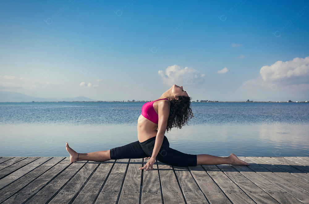 Woman doing a split on wooden pier at the sea