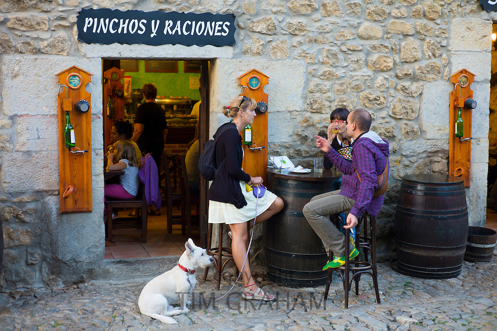 Locals at tapas bar, Pinchos Y Raciones, in cobbled street of Calle Del Canton in Santillana del Mar, Cantabria, Northern Spain
