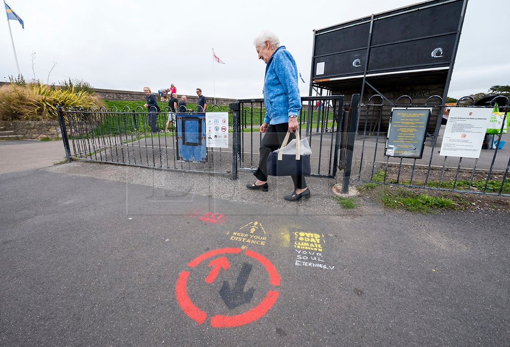 """© Licensed to London News Pictures; 09/09/2020; Clevedon, UK. Stencils are seen on the pathways by the Marine Lake advising people to keep social distancing during the coronavirus covid-19 pandemic. North Somerset has the highest infection rate in the South West of England. The stencils by North Somerset Council with their logo refer to cultural memes such as Star Trek """"Space the final frontier"""", the film Alien """"In Space no one can hear you sneeze"""", the song """"Don't Stand So Close To Me"""" by the Police and the world war one recruitment poster """"North Somerset needs you to keep your distance"""". Other stencils have been added referring to the climate crisis and global warming. Photo credit: Simon Chapman/LNP."""