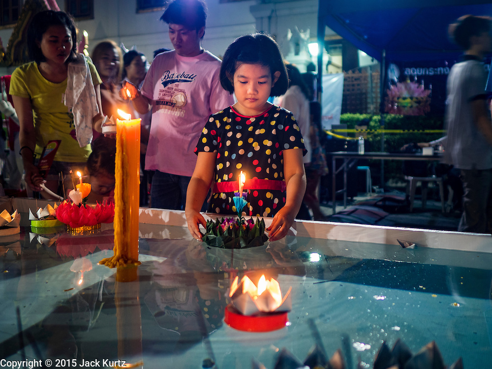 25 NOVEMBER 2015 - BANGKOK, THAILAND: A Thai girl floats her krathong in a small pool at the temple during Loy Krathong at Wat Yannawa in Bangkok. Loy Krathong takes place on the evening of the full moon of the 12th month in the traditional Thai lunar calendar. In the western calendar this usually falls in November. Loy means 'to float', while krathong refers to the usually lotus-shaped container which floats on the water. Traditional krathongs are made of the layers of the trunk of a banana tree or a spider lily plant. Now, many people use krathongs of baked bread which disintegrate in the water and feed the fish. A krathong is decorated with elaborately folded banana leaves, incense sticks, and a candle. A small coin is sometimes included as an offering to the river spirits. On the night of the full moon, Thais launch their krathong on a river, canal or a pond, making a wish as they do so.     PHOTO BY JACK KURTZ