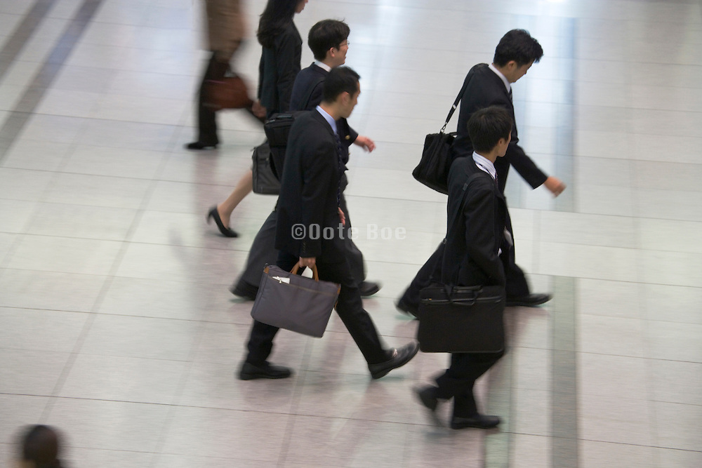 overhead view of group of young businessmen walking in one direction Japan Tokyo