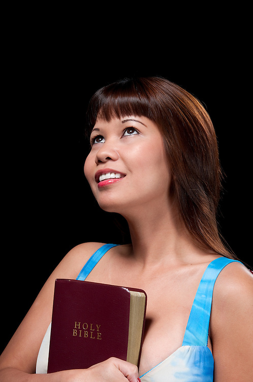 Young oriental woman holding faithful the Holy Bible.