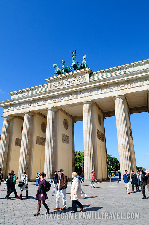 Brandenburg Gate (Brandenburger Tor) in Berlin, with tourists in the foreground and deep blue sky in the background.