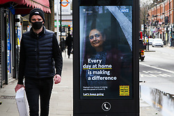 © Licensed to London News Pictures. 06/03/2021. London, UK. A man wearing a protective face covering walks past the government's 'Every day at home is making a difference' awareness poster in north London. The roadmap for the gradual reopening of the Covid-19 lockdown restrictions in England begins from Monday 8 March 2021. Primary and secondary schools will be the first to reopen in England, as the 'stay at home' guidance will change from 29 March 2021. Photo credit: Dinendra Haria/LNP