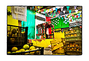SHOT 2/20/19 10:44:51 AM - A corner capilla hidden behind crates of fruit inside a fruit stand in the Mercado Municipal Lucas de Gálvez in Merida, Mexico. The capillas are often dedicated to certain patron saints, such as Nuestra Senora de Guadalupe. Our Lady of Guadalupe is a powerful and ubiquitous symbol of Mexican identity because some guess that Our Lady of Guadalupe's skin tone matches that of Mexico's indigenous population: light brown. She is as much revered for her striking similarity to the vanquished native Mexican population as she is for being the mother of God. Often times they contain prayer candles, pictures, personal artifacts or notes. Mérida is the capital and largest city in Yucatan state in Mexico, as well as the largest city of the Yucatán Peninsula. As the largest city in the Yucatan it has become a hub for commerce and culture. (Photo by Marc Piscotty / © 2019)