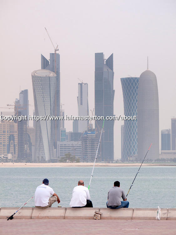 Men fishing  on The Corniche with modern office towers and skyline in business district in Doha Qatar