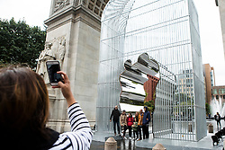 A woman takes picture of the Chinese activist and artist, Ai Weiwei's art project at Washington Square in New York,NY on October 12, 2017.   The artist assembeled 300 establishment around New York City statement  'Good Fences Make Good Neighbors'.  The works can be viewed through February 11, 2018. (Amir Levy/ SIPA USA)