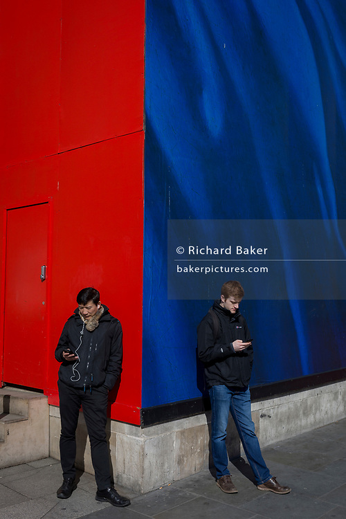 Two men check messages or social media on their smartphones, against a background of primary colours, on 21st March 2017, in London, England.