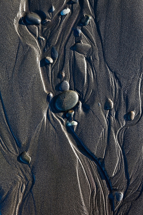 Water and rounded pebbles form abstract designs in the sand at Kalaloch Beach, Olympic National Park, Washington.