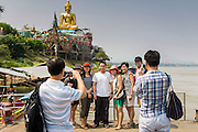 26 APRIL 2014 - CHAING SAEN, CHIANG RAI, THAILAND: Chinese tourists pose for photos in front of a large Buddha statue in the Golden Triangle, Chiang Saen district, Chiang Rai province, Thailand. Chinese businesses play an increasingly important role in the Chiang Rai economy. Consumer goods made in China are shipped to Thailand while agricultural products made in Thailand are shipped to China. Large Chinese cargo boats ply the Mekong River as far south as Chiang Saen in the dry season and Chiang Khong when river levels go up in the rainy season.      PHOTO BY JACK KURTZ
