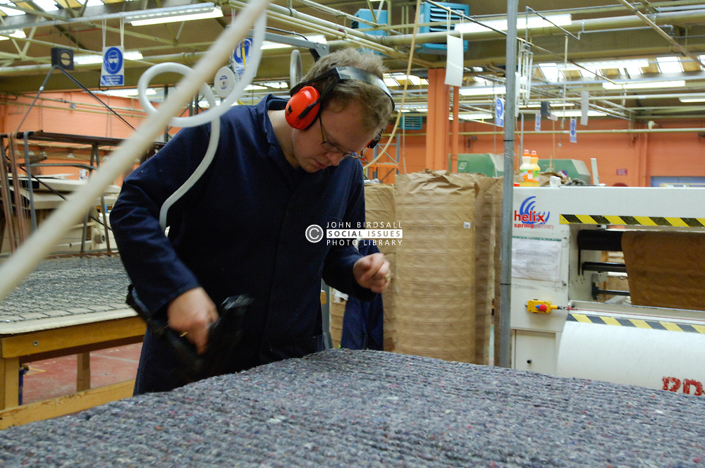 Remploy factory; Forest Hall; Newcastle; UK 2007, Remploy provides specialist employment services to disabled people and those who face barriers to employment, Man making mattress fastening down cover