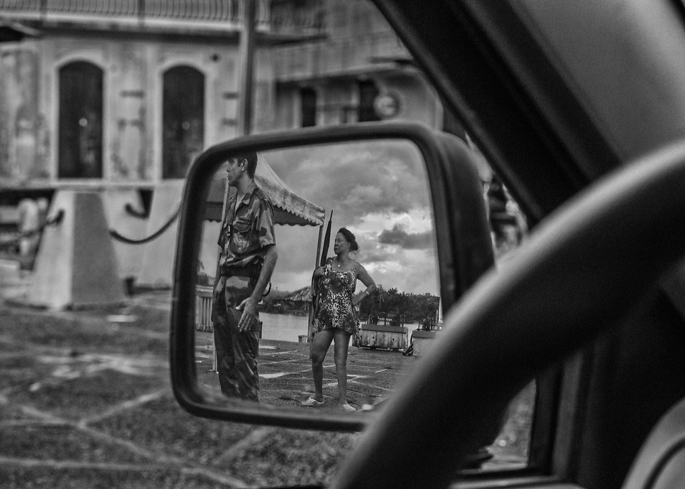 Saint-Georges de l'Oyapock, Guyane, 2015.<br /> <br /> Saint-Georges de l'Oyapock est un Chef-lieu de canton de 4000 habitants à la frontière Est du département au bord du fleuve Oyapock, à 190 Km de Cayenne soit 3 heure en taxi collectif et 10 minutes de pirogue d'Oiapoque sur la rive brésilienne. <br /> Les riverains sont ici géographiquement, mais aussi culturellement et économiquement plus proches de la berge opposée que de leurs capitales régionales. Les différentes communautés locales, amérindiennes, créoles ou brésiliennes admettent difficilement les réalités de la frontière et vivent indifféremment sur la rive droite ou la rive gauche du fleuve.<br /> <br /> Un pont a été construit entre les deux rives. Terminé depuis trois ans, il n'est toujours pas mis en service mais sa prochaine ouverture transforme cette zone de libre passage en zone douanière. Les services français de police et de gendarmerie y ont augmenté de manière significative leurs effectifs pour contrôler cette « nouvelle » frontière.<br /> Oiapoque, la ville jumelle brésilienne, compte cinq fois plus d'habitants mais avec un salaire minimum quatre fois moins élevé. Chaque jour, attirés par les gisements aurifères et les salaires guyanais, des dizaines de brésiliens passent clandestinement par le fleuve pendant que les touristes guyanais partent se ravitailler à moindre coût sur la rive brésilienne du fleuve.