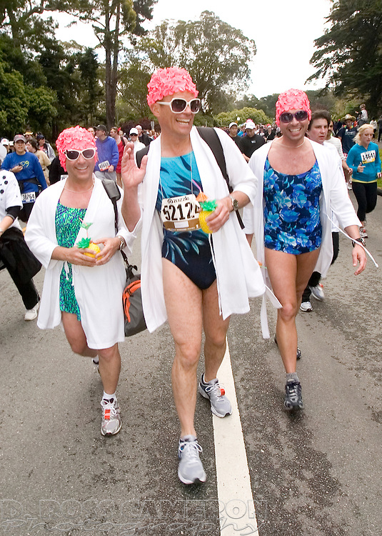 John Peichochi of Redwood City, Calif., from left, Chuck Roberts of Washington, D.C. and Break Eaker of Redwood City wore matching bathing caps as they walked through Golden Gate Park during the 100th running of the Bay to Breakers 12K in San Francisco, Sunday, May 15, 2011. (Photo by D. Ross Cameron)