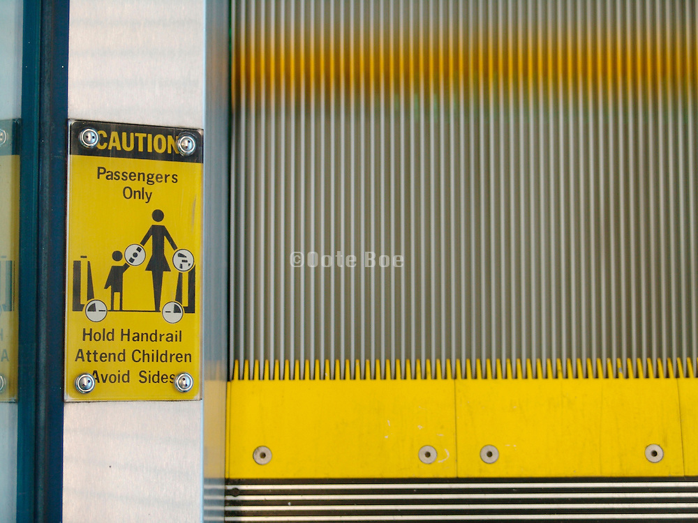 Close up of a warning sign to take caution when riding the escalator with a child.