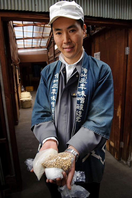 Ishii Miso vice-president, Kousuke Ishii holding the basic ingredients of miso, rice koji, soy beans and salt. Ishii Miso, Matsumoto, Japan, May 19, 2009. The miso company, founded in 1868, uses Japanese soy beans and wooden barrels to make premium miso aged for up to three years.