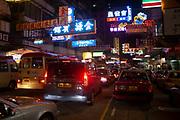 Traffic at night under neon signs in Hong Kong, China.