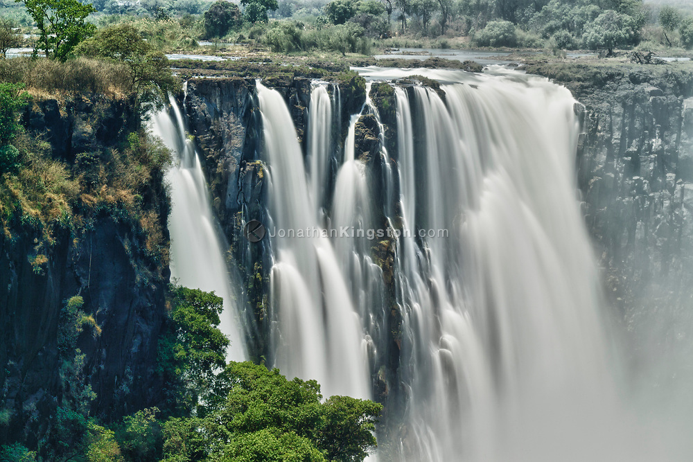 Views of Victoria Falls from Victoria Falls National Park, in the Hwange District of Matabeleland, in the North Province of Zimbabwe. The spectacular waterfalls of the Zambezi River are considered among the Seven Natural Wonders of the World, and are a main tourist destination in Southern Africa. The cascading water drops between 90 - 170 meters into the Zambezi Gorge, and are 1,708 meters wide during rainy season.