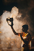 A Hindu priest lifts a smoking incense burner above his head during the daily Aarti ceremony, The Main Ghat, River Ganges, Varanasi, India