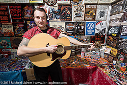 Vendor on guitar break in the Custom and Tuning Show, the custom bike show portion of the big Motor Spring bike show in Moscow, Russia. Sunday April 23, 2017. Photography ©2017 Michael Lichter.