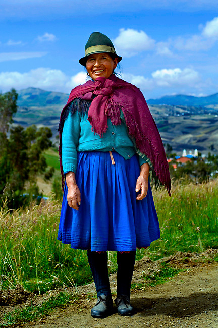 Felt brown hat, shawl, and blue dress help to identify this indigeneous woman's ethnicity and traditions in the Andes of Ecuador