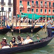 Gondolas with tourists in Venice harbor (Italy)