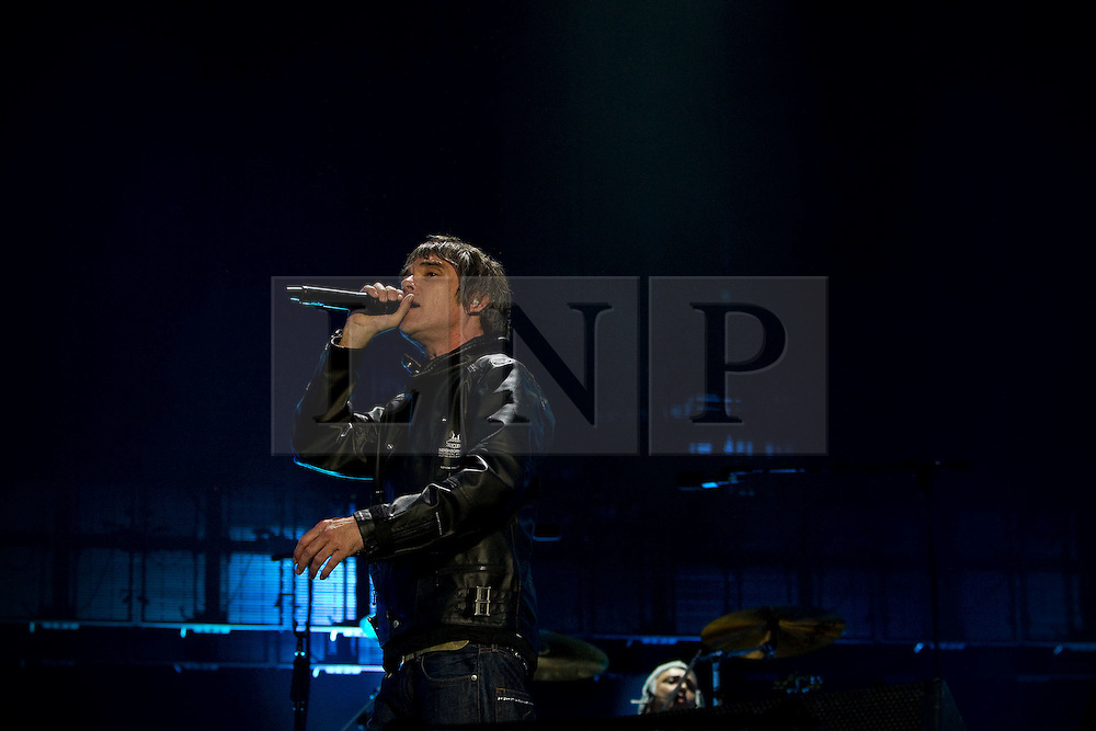© licensed to London News Pictures . 30/06/2012 . Manchester , UK . Ian Brown fronts The Stone Roses on stage at Heaton Park during the band's comeback event . Drummer , Reni , is in the background . Photo credit : Joel Goodman/LNP