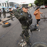 A soldier tries to hit the photographer with a baton. Many journalists have lost their lives in Honduras since the 2009 coup, and intimidation of any journalist who doesn't work for an approved media outlet is routine.