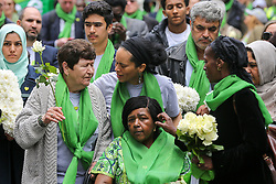 © Licensed to London News Pictures. 14/06/2019. London, UK.  Survivors, family and friends of the victims wear symbolic green scarves to commemorate the second anniversary of the Grenfell Tower fire. On 14 June 2017, just before 1:00 am a fire broke out in the kitchen of the fourth floor flat at the 24-storey residential tower block in North Kensington, West London, which took the lives of 72 people. More than 70 others were injured and 223 people escaped. Photo credit: Dinendra Haria/LNP