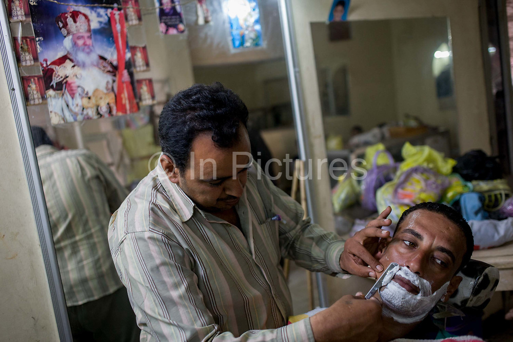 A young Egyptian man has a shave from the local barber in Bairat, a village on the West Bank of Luxor, Nile Valley, Egypt. With his lathered face on which his stubble shows through, he turns away and lets the barber pass the blade towards his mouth.
