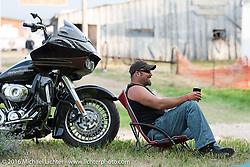 Craig Needham relaxes next to his Road Glide at the Buffalo Chip Campground during the annual Sturgis Black Hills Motorcycle Rally.  SD, USA.  August 6, 2016.  Photography ©2016 Michael Lichter.