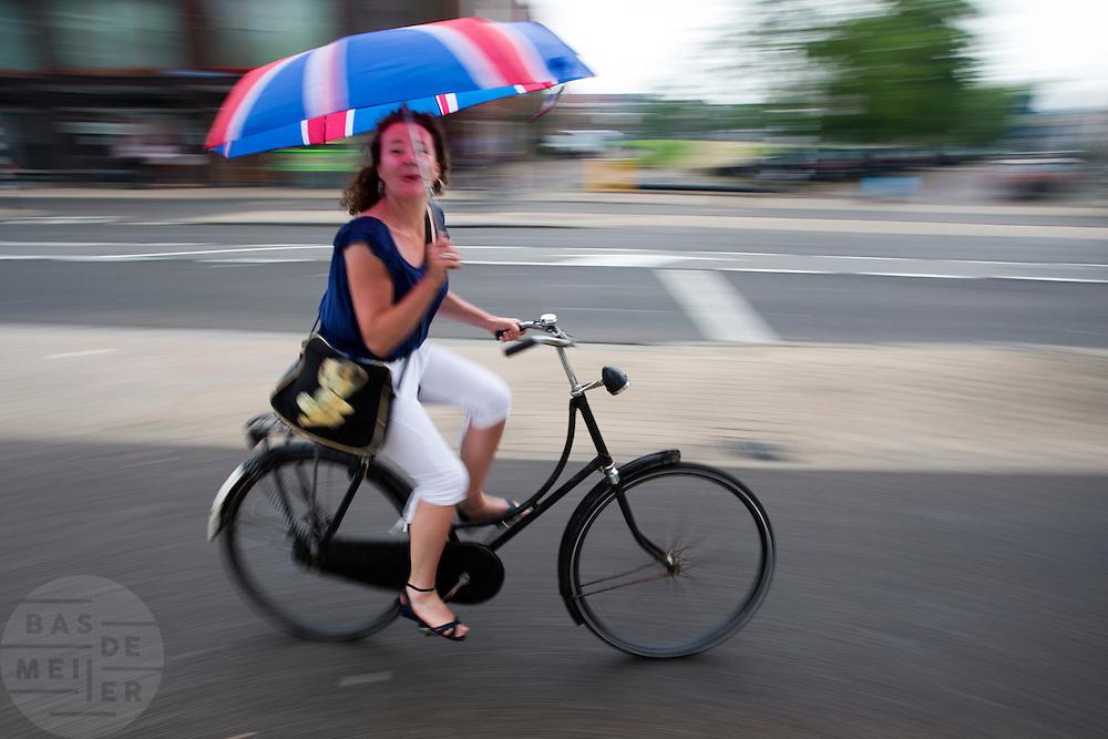 Een vrouw fietst met een paraplu met de Engelse vlag door een zomerse regenbui.<br /> <br /> A woman is cycling with an umbrella in the rain.