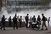 Children and adults playing in the fog installation by Japanese artist Fujiko Nakaya outside Tate Modern. London. 12 April 2017