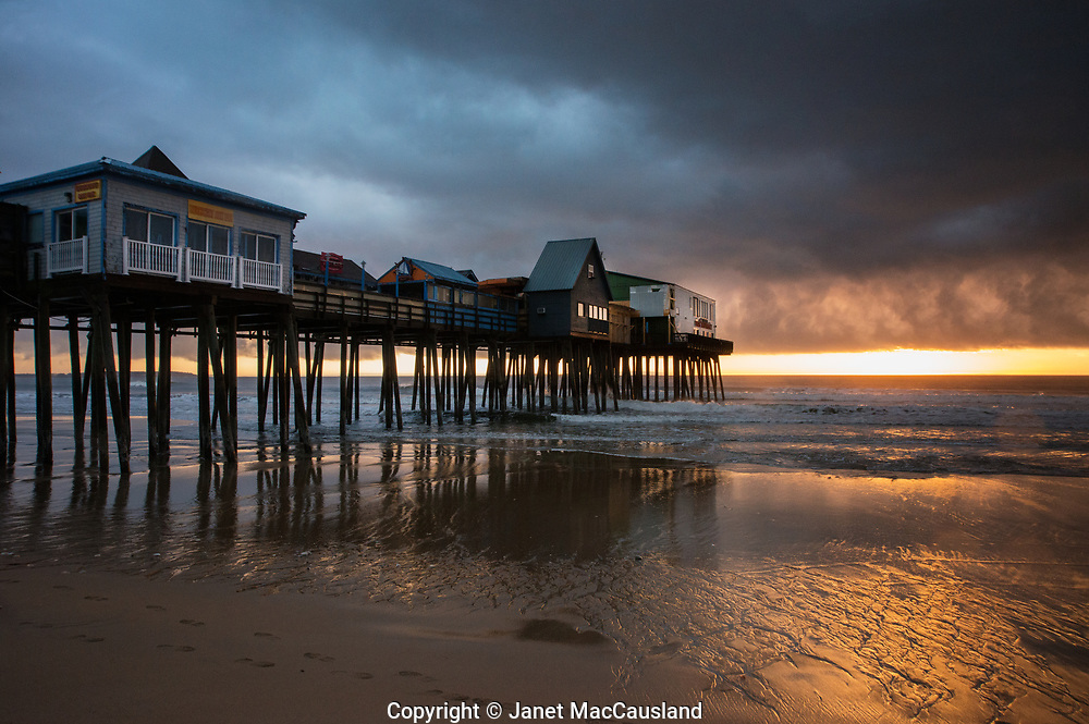 A storm crowds out the sunrise at Old Orchard Beach pier in Down East Maine.