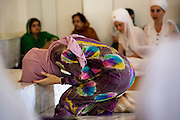12 AUGUST 2012 - PHOENIX, AZ:  A member of the Phoenix Sikh community touches her forehead to the ground and  makes an offering to the Guru during Sunday services at the Guru Nank Dwara Ashram Sikh temple in central Phoenix. Guru Nank Dwara Ashram is the oldest of three Sikh temples in the Phoenix area. There are about 1,500 Sikh families in the area. Memorials have been held throughout the week to honor the Sikhs killed in the mass shooting in Wisconsin last week. Sunday's service included several mentions of the massacre and was attended by a number of people active in the Phoenix interfaith community.   PHOTO BY JACK KURTZ